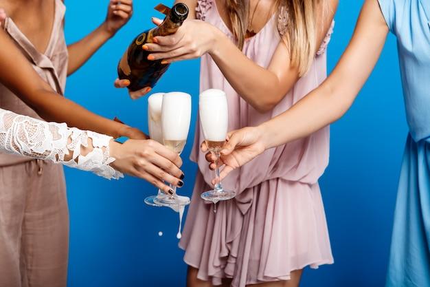 Feche a foto das mãos das meninas segurando copos com champanhe.