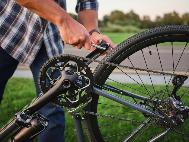 Feche a foto das mãos de um homem consertando os pedais de sua bicicleta em público