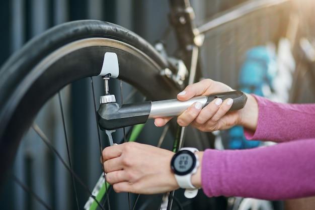 Feche a foto das mãos de uma ciclista profissional usando uma bomba para inflar o pneu