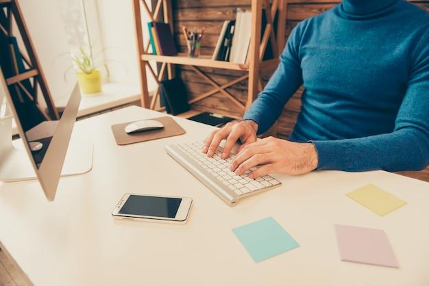 Feche a foto das mãos do homem digitando no teclado
