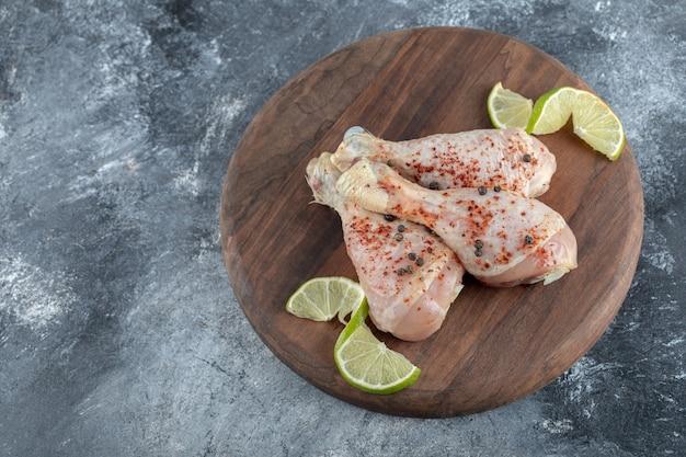 Feche a foto das pernas de frango cru marinado na placa de madeira sobre o fundo cinza.