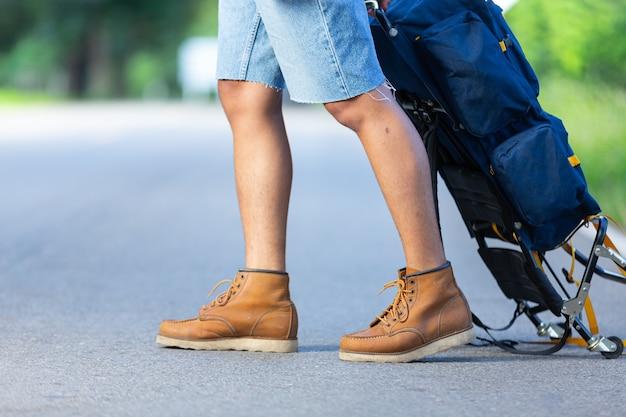 Feche a foto das pernas do viajante em uma estrada rural