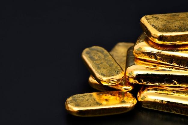 Feche a foto de barras de ouro no espaço de cópia da parede preta