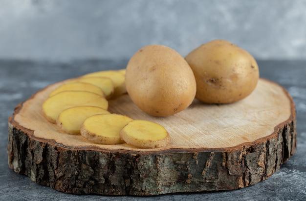 Feche a foto de batatas fatiadas e inteiras na placa de madeira.