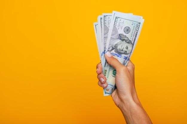 Feche a foto de belas mãos femininas segurando o monte de dólares dos eua isolado em fundo amarelo. conceito de economia, negócios e finanças