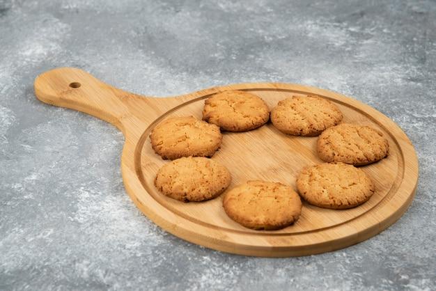 Feche a foto de biscoitos caseiros frescos em uma placa de madeira sobre uma superfície cinza