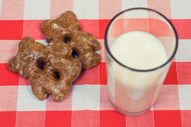 Feche a foto de biscoitos e copo de leite na toalha de mesa quadriculada