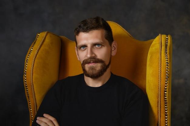 Feche a foto de bonito homem com a barba por fazer, com olhos azuis, barba difusa e bigode relaxantes dentro de casa, sentado isolado em uma poltrona elegante. conceito de pessoas, estilo, design de interiores e móveis
