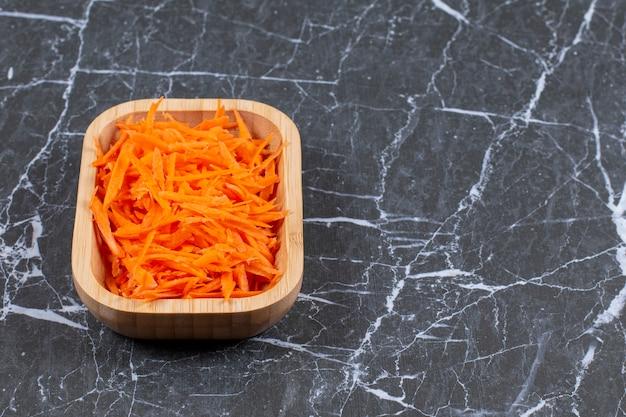Feche a foto de cenoura fresca ralada em uma tigela de madeira marrom.