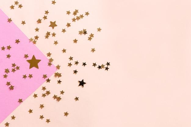Feche a foto de confetty de brilho de forma de estrela rosa sobre fundo rosa colorido. vista superior, primavera, páscoa e vários conceitos de feriados e eventos