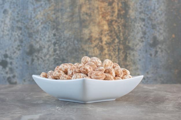 Feche a foto de doces de caramelo em uma tigela branca.