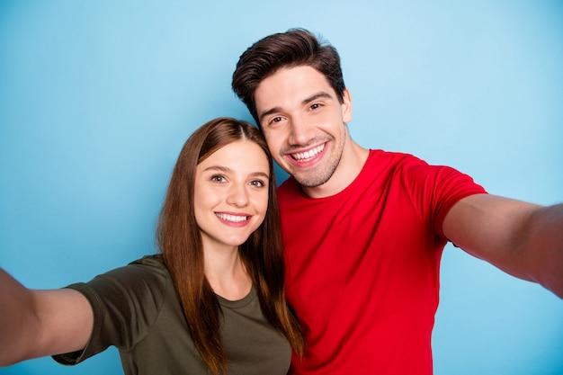 Feche a foto de dois apaixonados e sonhadores casados, estudantes, relaxe, descanse, abrace, abraço, faça uma selfie na viagem de verão, use uma camiseta vermelha verde isolada sobre um fundo de cor pastel