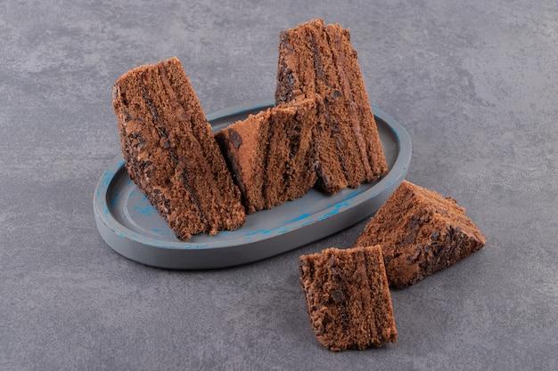 Feche a foto de fatias de bolo de chocolate caseiro na placa de madeira