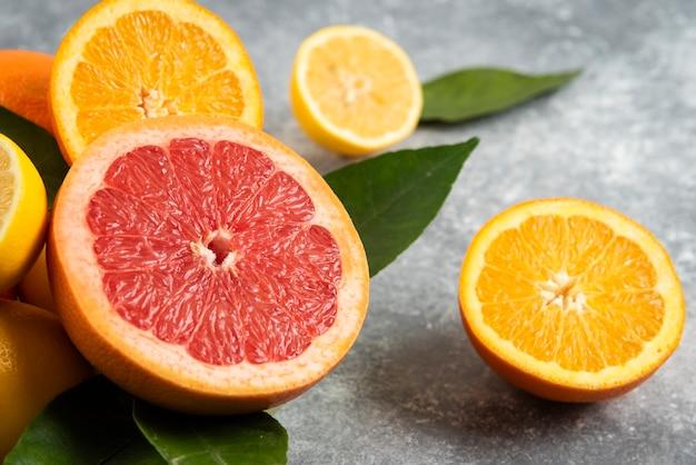 Feche a foto de frutas cítricas fatiadas na superfície cinza.