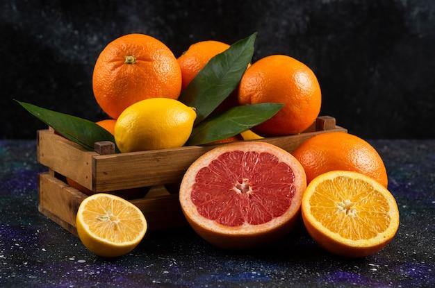 Feche a foto de frutas cítricas frescas cortadas inteiras ou pela metade. .
