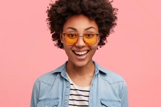 Feche a foto de hipster feminina com pele preta, cabelo encaracolado, sorri positivamente, usa óculos escuros e camisa jeans, regozija-se com o momento positivo da vida, feliz por fazer compras no fim de semana, isolado no rosa