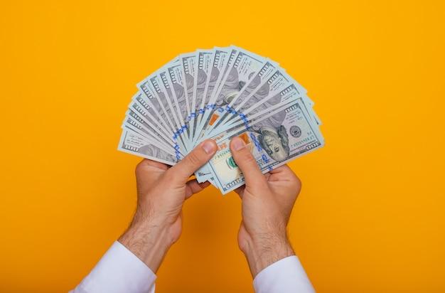 Feche a foto de jovens do sexo masculino segurando muitos dólares dos eua isolados em fundo amarelo