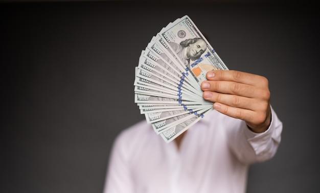 Feche a foto de jovens do sexo masculino segurando muitos dólares dos eua isolados em um fundo cinza