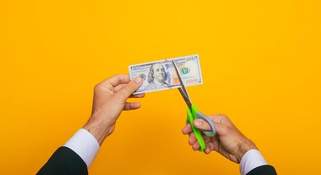 Feche a foto de jovens mãos humanas enquanto corta cem dólares com a ajuda de uma tesoura