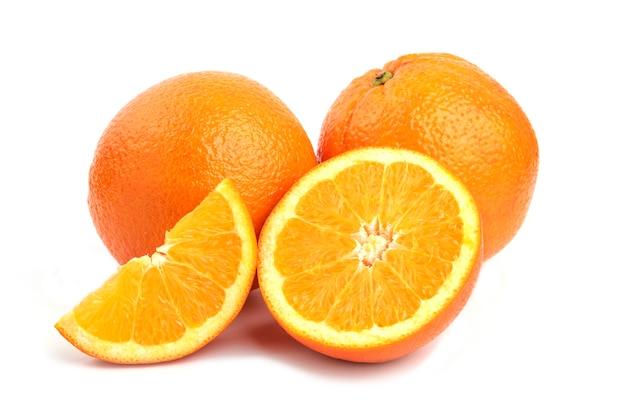Feche a foto de laranjas inteiras ou fatiadas, isoladas na superfície branca.
