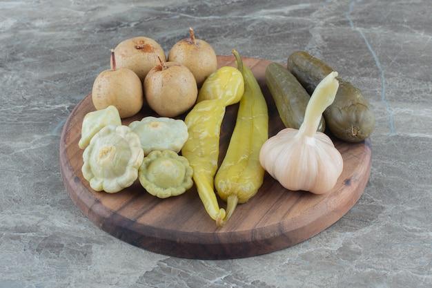 Feche a foto de legumes em conserva caseiros na placa de madeira.