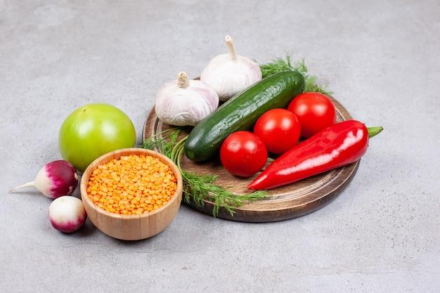 Feche a foto de legumes frescos na placa de madeira com uma tigela de lentilha.
