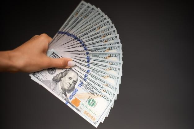 Feche a foto de lindas mãos femininas segurando o monte de dólares dos eua isolado no fundo cinza. conceito de economia, negócios e finanças