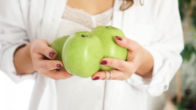 Feche a foto de mãos femininas segurando três maçãs verdes