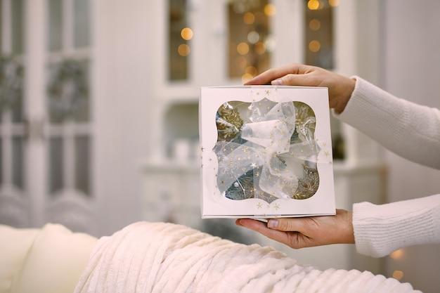 Feche a foto de mãos femininas segurando um presente