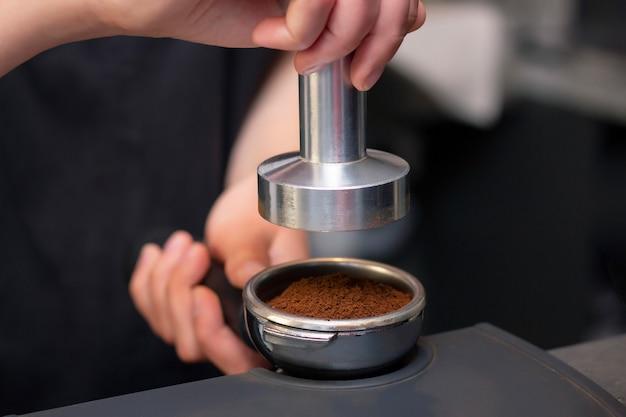 Feche a foto de mãos femininas segurando uma calcadeira de metal e um porta-filtro com café em uma cafeteria.