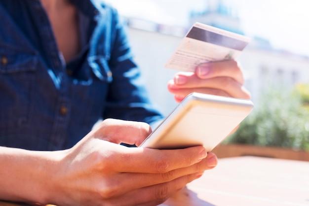 Feche a foto de mãos femininas usando smartphone e cartão de crédito para fazer compras online