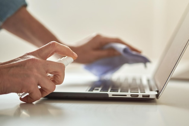 Feche a foto de mãos femininas usando spray desinfetante antibacteriano enquanto desinfeta o laptop