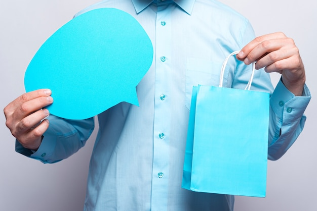 Feche a foto de mãos masculinas segurando um balão de fala vazio e uma sacola de compras.