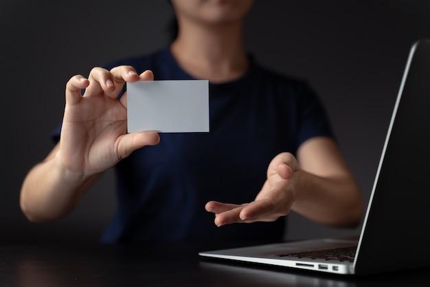 Feche a foto de mãos mostrando o cartão de visita e trabalhando com o laptop.
