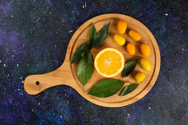 Feche a foto de meia laranja cortada com folhas e kumquats.