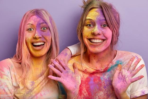 Feche a foto de mulheres alegres e sorridentes em alto astral, sorria amplamente, mostre as palmas das mãos, tenha rostos sujos e palmas com as cores holi, divirta-se em ambientes internos, isolados sobre a parede roxa. celebração
