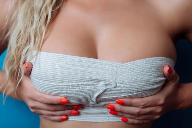 Feche a foto de peitos grandes em bandagem após a cirurgia, tamanho sexual. bandagem aumento de mama