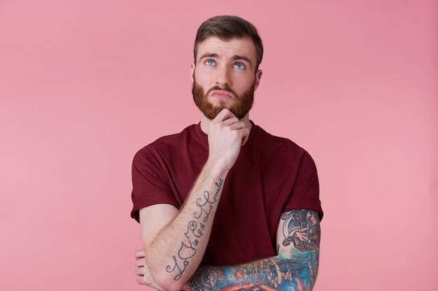 Feche a foto de pensar jovem barbudo macho com mão tatuada, segurando o punho no queixo, olhando de lado isolado sobre fundo rosa. esperando por inspiração.
