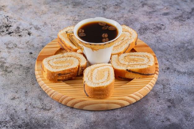 Feche a foto de rolos de bolo fresco com uma xícara de café.