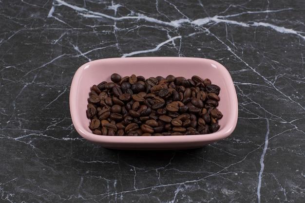 Feche a foto de sementes de café marrom em uma tigela rosa.