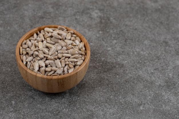 Feche a foto de sementes de girassol descascadas em uma tigela de madeira sobre a superfície cinza.