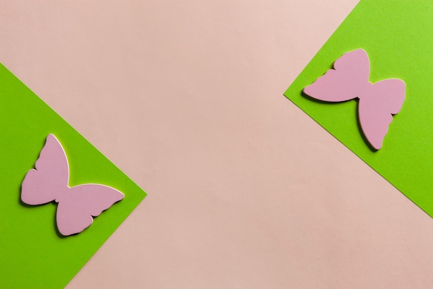 Feche a foto de silhuetas de borboletas cor de rosa em fundo verde e rosa colorido. vista superior, primavera, conceito de páscoa