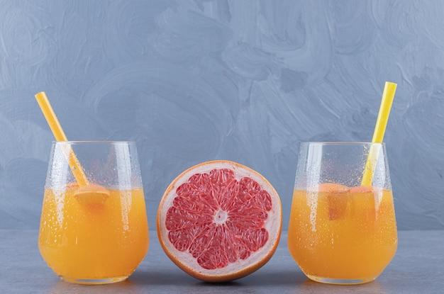 Feche a foto de suco de laranja acabado de fazer com toranja madura em fundo cinza.