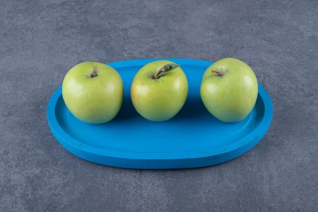 Feche a foto de três maçãs frescas na placa de madeira azul.