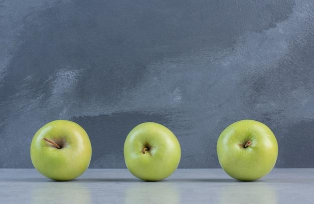 Feche a foto de três maçãs verdes frescas.