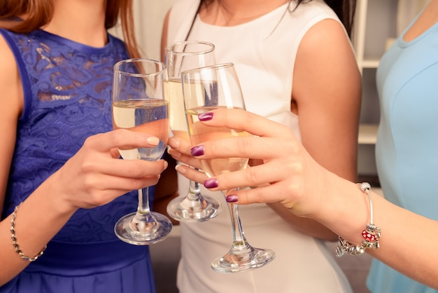 Feche a foto de três mãos levantando copos com champanhe em um brinde