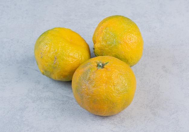 Feche a foto de três tangerinas frescas.