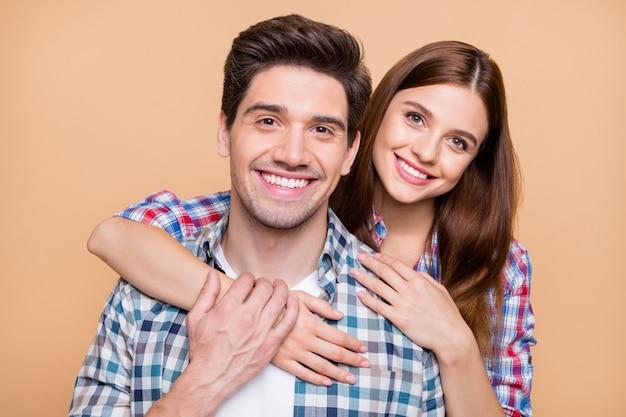 Feche a foto de um casal alegre, positivo e fofo de duas pessoas brancas sorrindo, amando-se e admirando afetuosamente a empresa isolada sobre um fundo bege