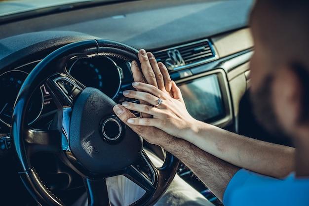 Feche a foto de um casal apaixonado, viajando de carro e segurando a mão, foco de fundo de verão nas mãos
