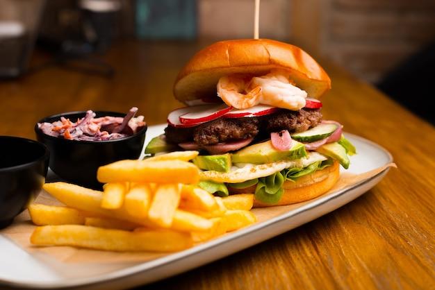 Feche a foto de um delicioso hambúrguer e batatas fritas em uma mesa de madeira.
